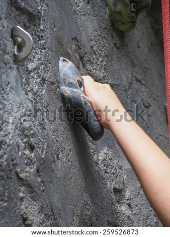 Hand hanging the rock on rock climbing - stock photo