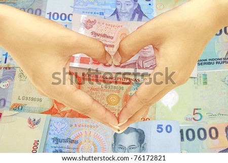 Hand heart with asia money background - stock photo