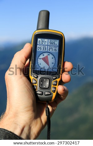 Hand held outdoor GPS being used for navigation in the mountains. - stock photo