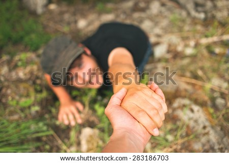 Hand helping a man to raise after falling - stock photo