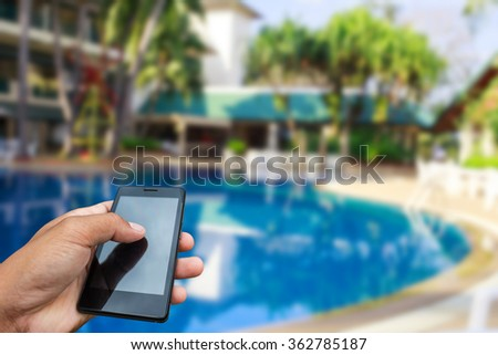 Hand hold and touch screen smart phone, tablet,cellphone over swimming pool,blurred filter effect - stock photo