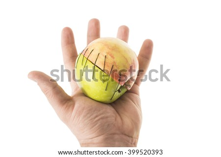 hand hold apple part manipulated fruit with thread ceep couple together forced unification two parts in one surgery Organ Transplantation mergers idea weddings marriage sex union between breeding - stock photo