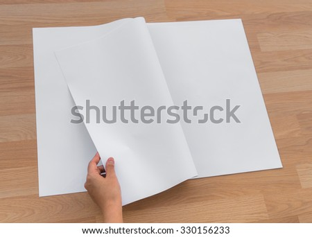 Hand hold Blank Newspaper with empty space mock up on wood background - stock photo