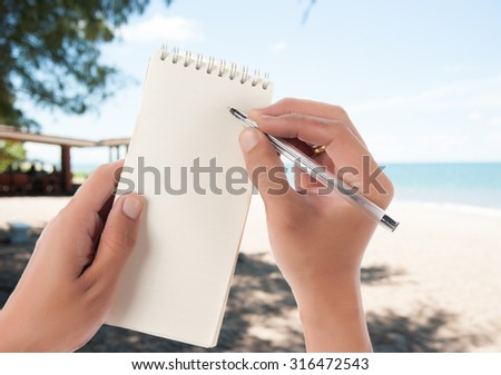 Hand hold blank notepad with space for text,blur beach background - stock photo