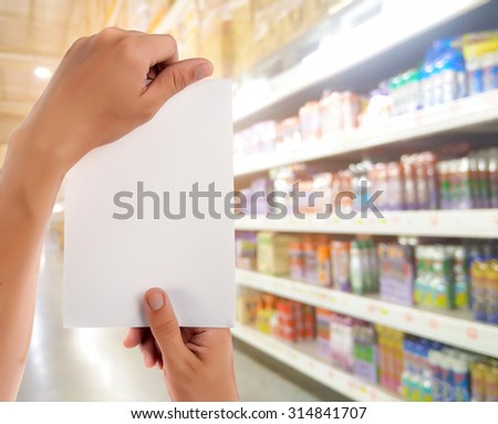Hand hold blank notepad with space for text,Supermarket blur background - stock photo