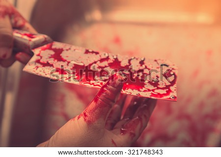 Hand hold bloody knife in a steel shell for halloween ( Filtered image processed vintage effect. ) - stock photo