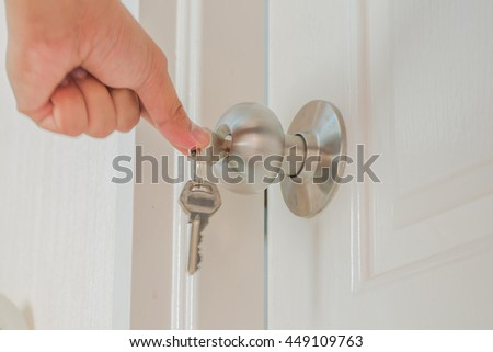 Hand hold door knob and open the white door with private key as locksmith concept. - stock photo