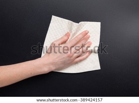 Hand hold dry cleaning cloth. Woman's hand clean kitchen black table - stock photo