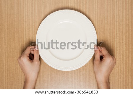 hand hold empty plate on wood table - stock photo
