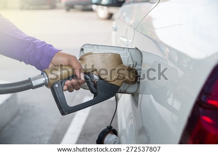 Hand hold Fuel nozzle to add fuel in car at filling station - stock photo