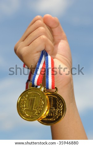 hand hold gold medal in blue sky background - stock photo