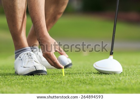 Hand hold golf ball with tee on course - stock photo