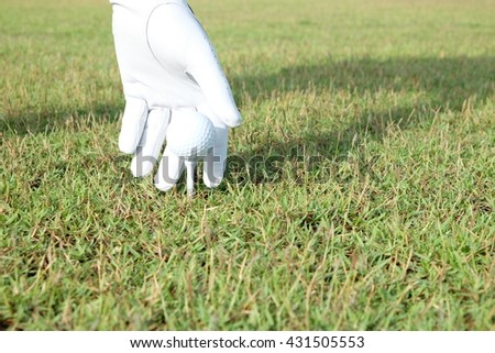 Hand hold golf ball with tee on course, close-up - stock photo