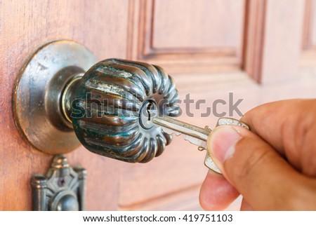 Hand hold house key to locking or unlocking the door - stock photo