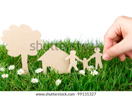 Hand hold paper cut  of family over  fresh spring green grass - stock photo