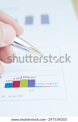 Hand hold pen point over financial graph - stock photo