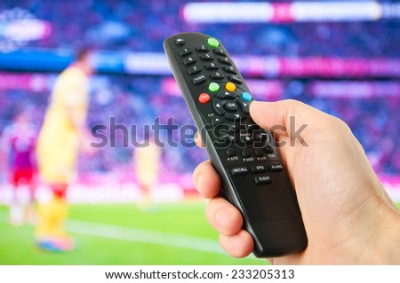 Hand hold remote control in front of tv  - stock photo