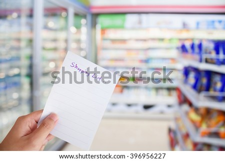 hand hold shopping list paper with convenience store refrigerator shelves blurred background - stock photo