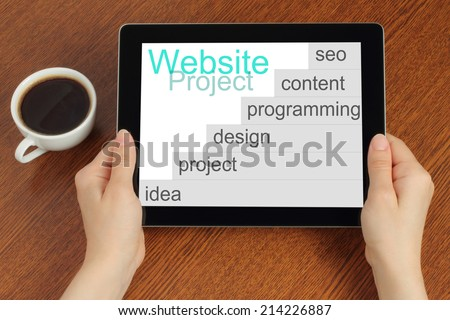 Hand hold tablet pc with website project's development steps on wooden background  - stock photo