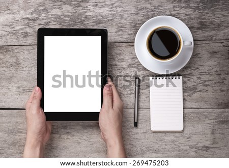 hand hold the empty tablet with note paper and coffee on the wooden table - stock photo