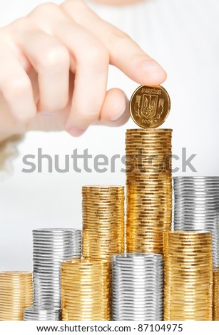 Hand hold ukrainian coin on the top of the stack - stock photo