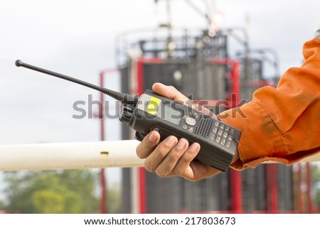 Hand hold walkie talkie on site in plant - stock photo