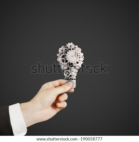 hand holdig light bulb with gears and cogs - stock photo