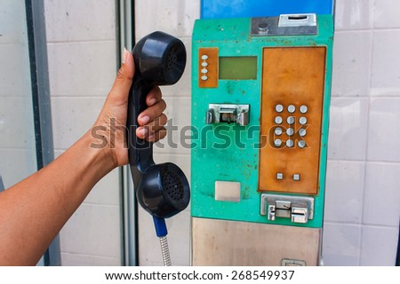 Hand holding a black handset of a public telephone - stock photo