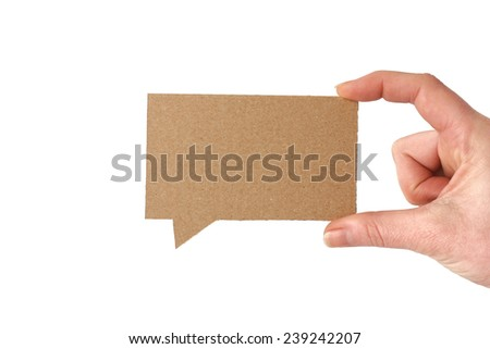 Hand holding a blank cardboard speech bubble - stock photo
