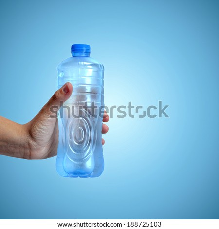 Hand holding a bottle of water on blue background - stock photo