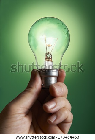 hand holding a bulb with globe on green background - stock photo