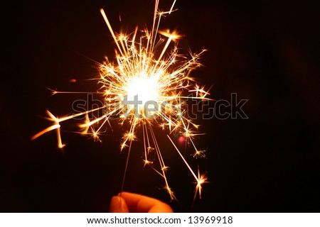 hand holding a burning sparkler - stock photo
