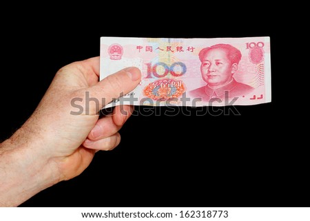 Hand Holding a Chinese One Hundred Yuan Note isolated on black - stock photo