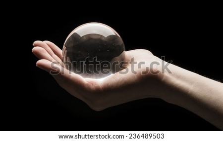 Hand holding a clear transparent crystal glass ball in their palm isolated on black background - stock photo