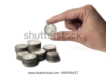 Hand holding a coin besides some piles of old coins of Brazil isolated over white background. - stock photo