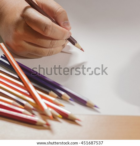Hand holding a colored pencil and draw.  Putting colored pencils the clutter on a white paper. - stock photo