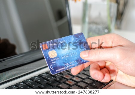 Hand holding a credit card over a laptop - stock photo
