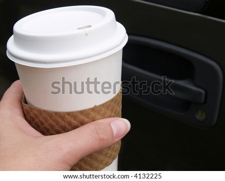 hand holding a disposable coffee cup outside of a car - stock photo