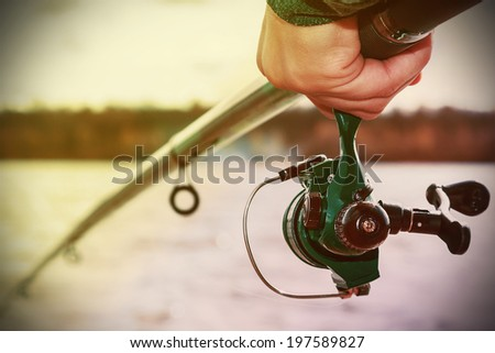hand holding a fishing rod with reel. Focus on Fishing Reels. Toned image - stock photo