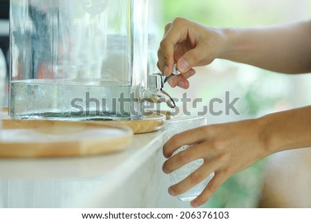 Hand holding a glass of water poured faucet - stock photo
