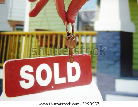 Hand holding a house key in front of a  sold sign - stock photo