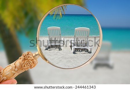 Hand holding a magnifying glass or loop, looking in on  tropical beach chairs in sand at the shoreline in the Caribbean with palm  tree - stock photo