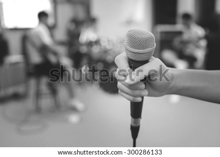 hand holding a microphone on musician blurred background on back and white style  - stock photo