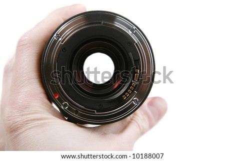 Hand holding a 35-mm photographic lens - stock photo