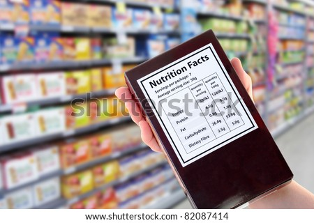 Hand holding a packet with nutritional information in supermarket - stock photo