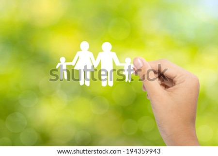 Hand holding a paper family on green background, insurance concept  - stock photo