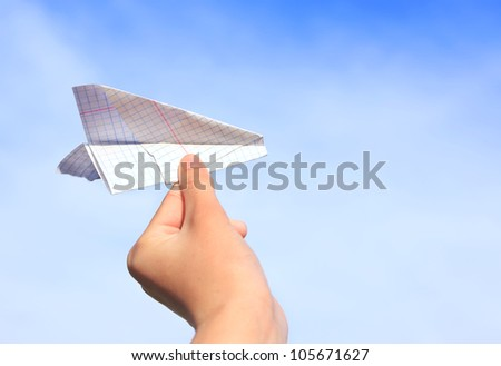 Hand holding a paper plane on a sky background - stock photo