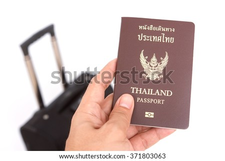 Hand holding a passport and bag on white background - stock photo
