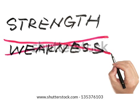 Hand holding a pen and choosing between strength and weakness - stock photo