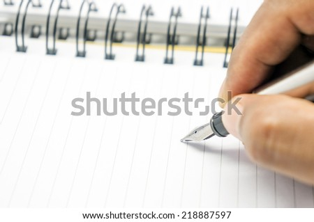 hand holding a pen on a white background books - stock photo